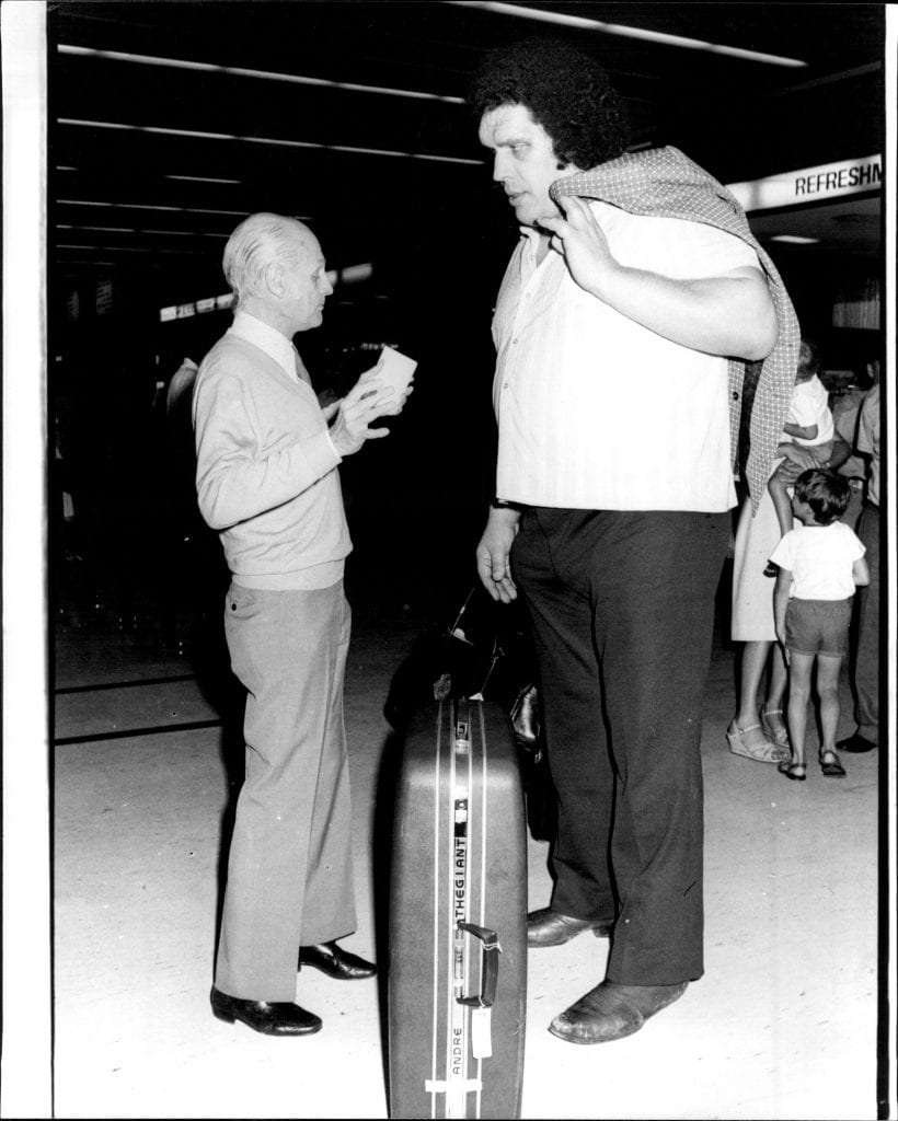 "The Largest picture of the day would have to be, ""Andre The Giant"" 31, the French Wrestler, 7 foot 5 inches and 35 stone. Andre, who visited Australia last year, is here for only one week, and will Wrestle at Flemington Markets tonight.Pictured with Heral"