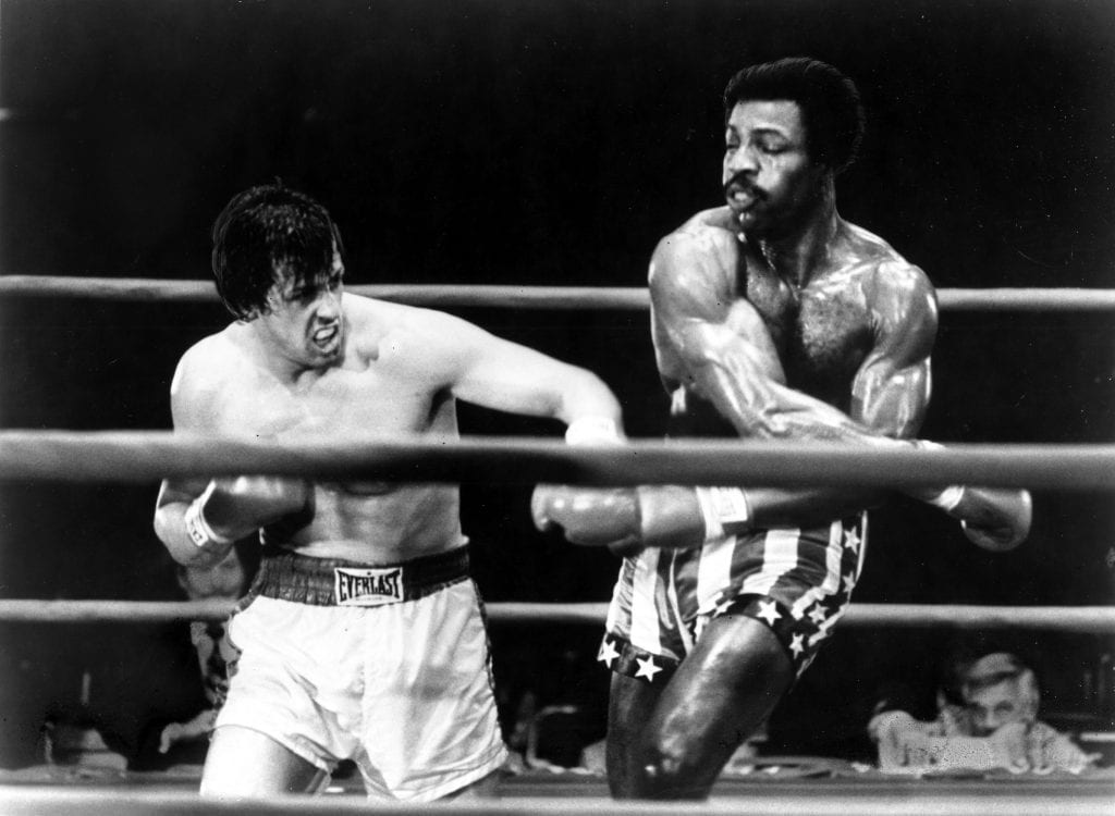 "1977: Actors Sylvester Stallone and Carl Weathers perform boxing scene in movie ""Rocky"" directed by John G. Avildsen. ""Rocky"" won 3 Academy Awards. (Photo by Michael Ochs Archives/Getty Images)"