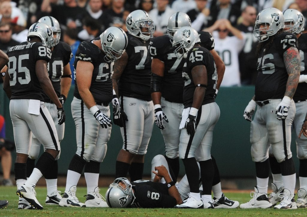 Oakland Raiders quarterback Jason Campbell, #8, lays on the ground injured