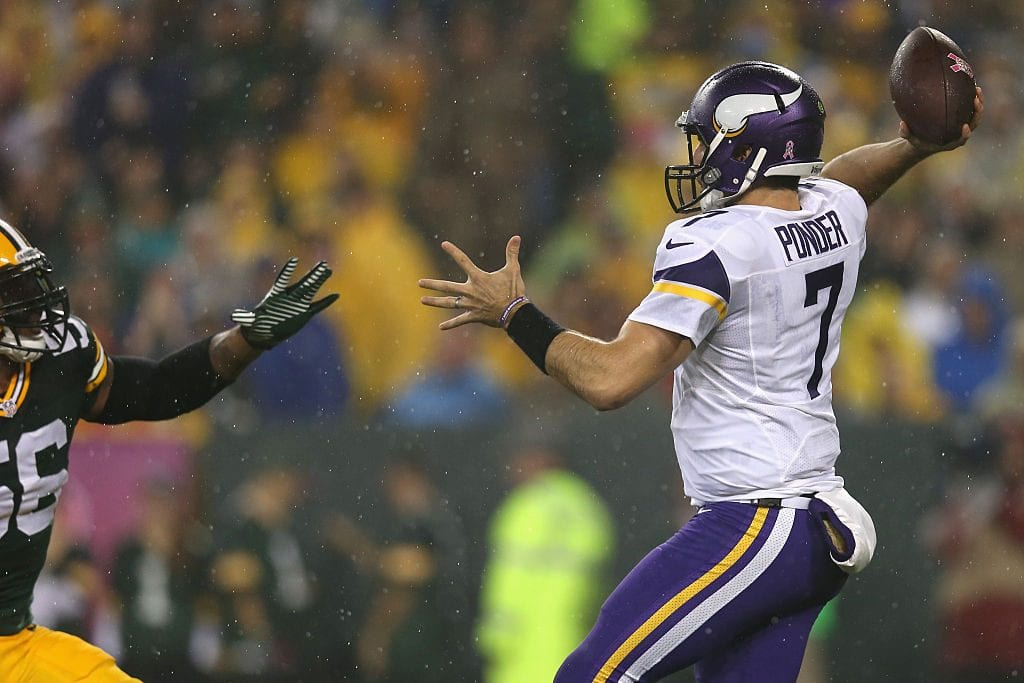 Quarterback Christian Ponder #7 of the Minnesota Vikings passes against Julius Peppers #56
