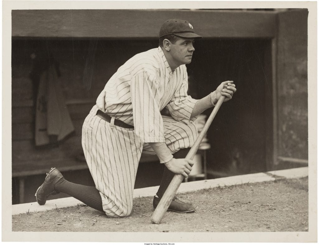Babe Ruth kneels with a baseball bat