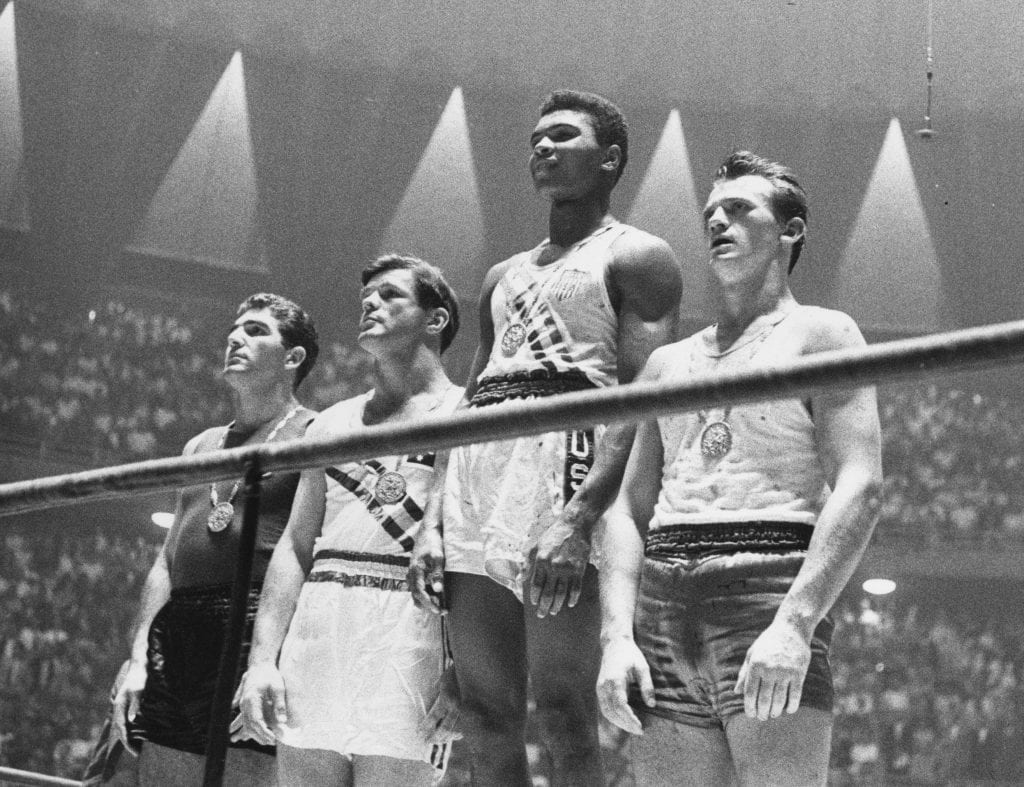 Cassius Clay (now Muhammad Ali) (C), gold; Zbigniew Pietrzykowski of Poland (R), silver; and Giulio Saraudi (Italy) and Anthony Madigan (Australia), joint bronze.