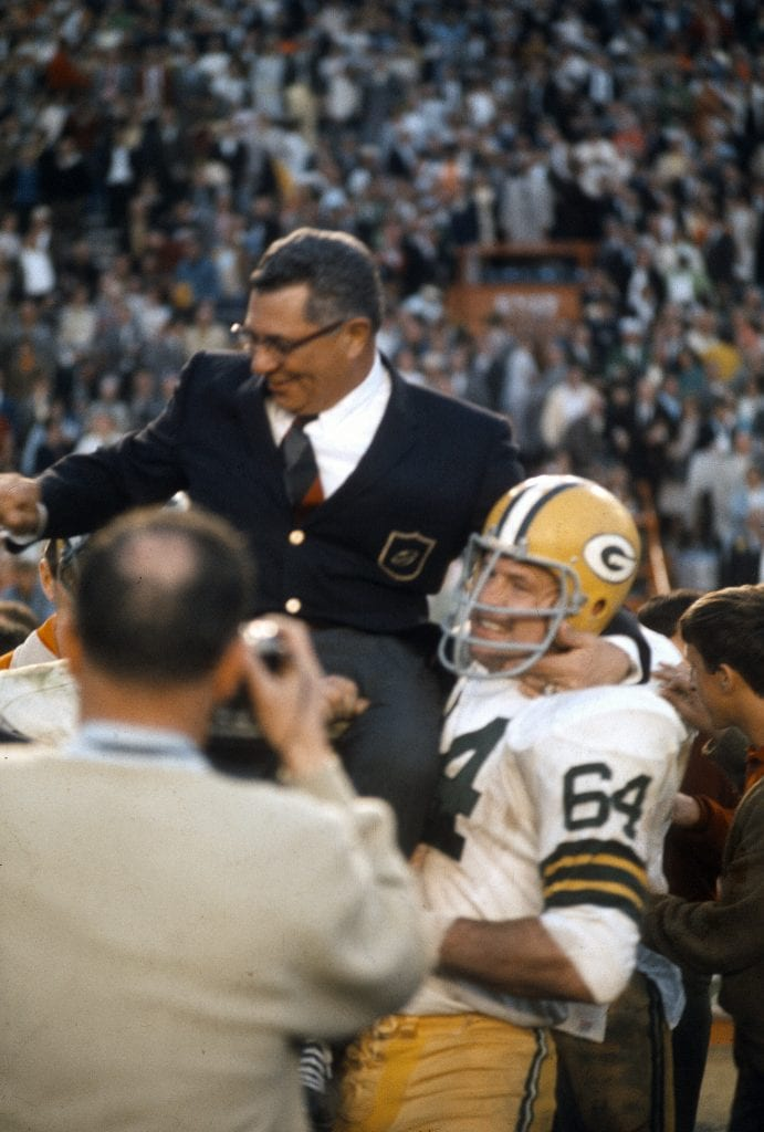 Head Coach Vince Lombardi (dark Jacket) of the Green Bay Packers gets carried off the field by Jerry Kramer