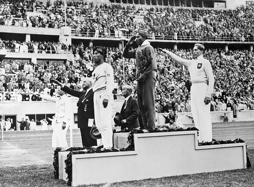 The gold, silver and bronze medal winners in the long jump competition salute from the victory stand at the 1936 Summer Olympics in Berlin. From left, Japan's Naoto Tajima (bronze), American Jesse Owens (gold) who set an Olympic record in the event and offers an American-style salute with his hand to his forehead, and Germany's Luz Long (silver) giving a Nazi salute with his arm extended out. August 8, 1936. Photo by Bettman, Getty Images