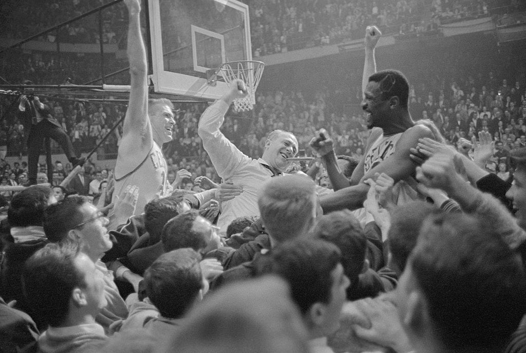 It's a jubilant mob scene as happy fans carry Celtics' Tommy Heinsohn (L), coach Red Auerbach (Center, with victory cigar), and big Bill Russell (R) around the basketball court at Boston Garden April 27th, after the Celtics won their sixth consecutive World's Championship. They defeated the Warrior's, 105-99. The Celtics are the only pro team in history to win six consecutive championships.