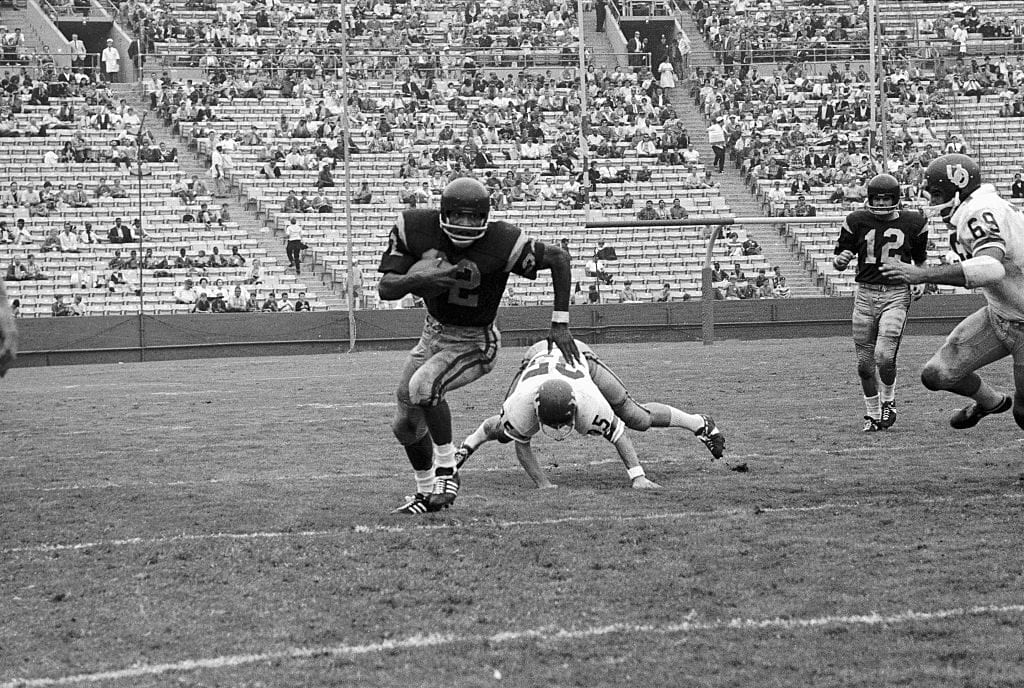 O.J. Simpson (#32) of USC, takes a handoff from Quarterback Steve Sogge (#12), and goes around right end for a gain of 8 yards. Simpson breaks loose from Oregon's Jack Gleason, (35), in this first quarter action.