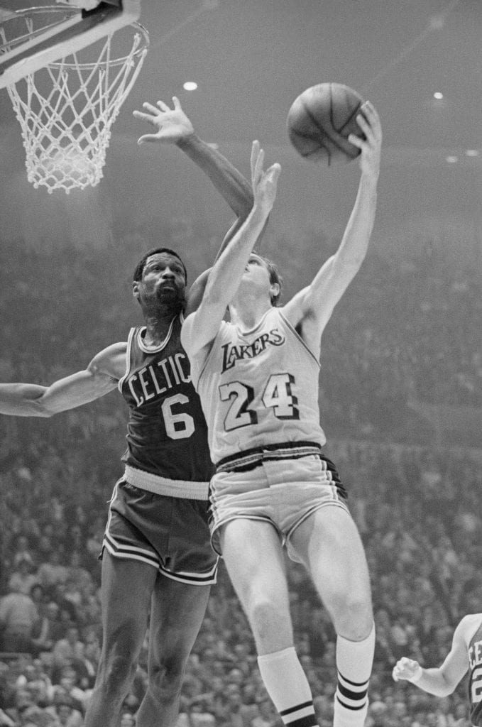 Boston's player coach Bill Russell blocks a shot by Keith Erickson