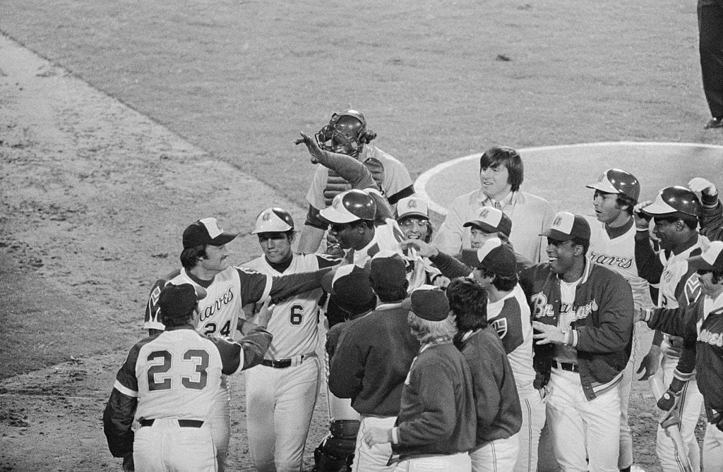 With his hand held aloft, Hank Aaron leaps into a host of cheering teammates after he hit his 715th home run