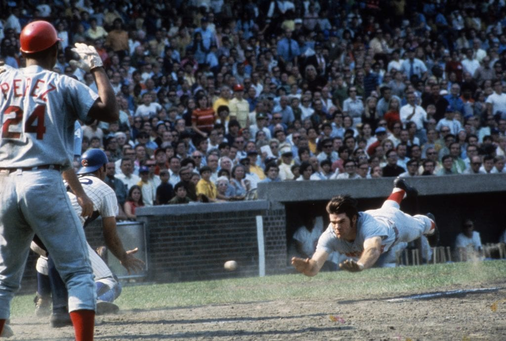 Pete Rose #14 of the Cincinnati Reds dives head first into home plate during a game against the Chicago Cubs at Wrigley Field during the early 1970s in Chicago