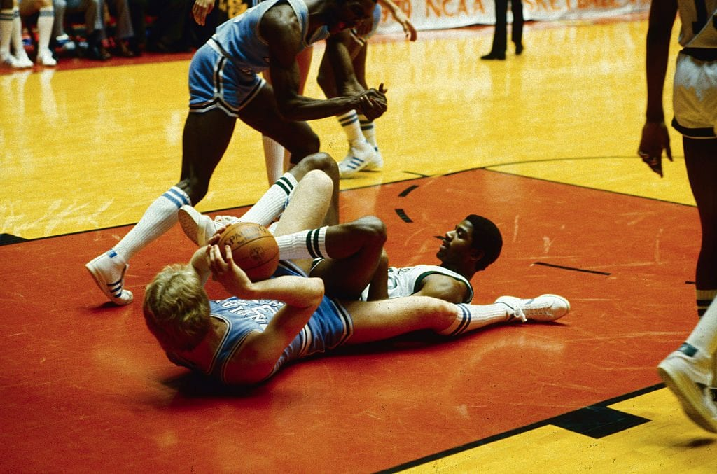 Indiana State's Larry Bird (L) and Michigan State's Earvin Johnson are a tangle on the floor under the Michigan State basket