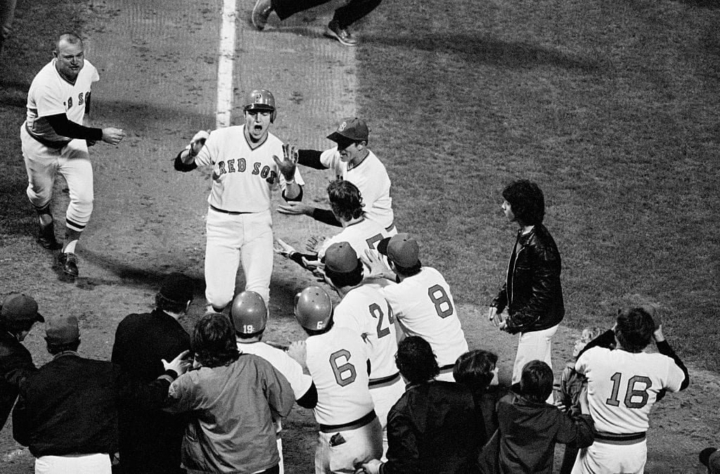 Red Sox catcher Carlton Fisk is greeted by his teammates at home plate after hitting the scoring run in game 6 of the 1975 World Series against the Cincinnati Reds.