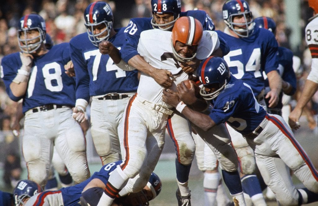 Cleveland Browns running back Jim Brown #32 tries to run with the ball as two New York Giants tackle him. Jim Brown played for the Browns from 1957-1965. (Photo by Focus on Sport via Getty Images)