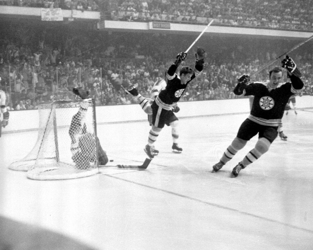 Bobby Orr #4 of the Boston Bruins flies through the air after sliding the puck past goalie Glenn Hall