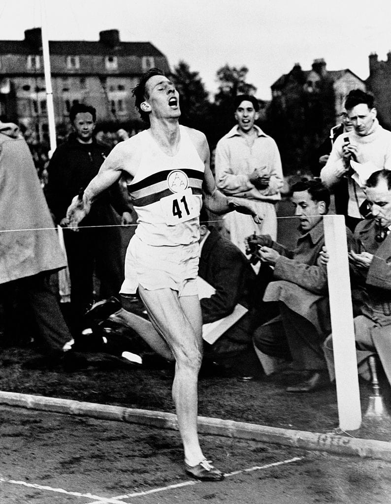 Roger Bannister breaks the tape as excited onlookers check their watches to find that Bannister has run the first ever sub-four minute mile