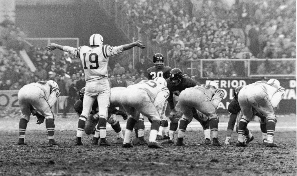 American football player Johnny Unitas, quarterback for the Baltimore Colts, holds his arms out to request quiet from the crowd for the final drive in the 1958 championship game against the New York Giants at Yankee Stadium in the Bronx, New York, New York, December 28, 1958.