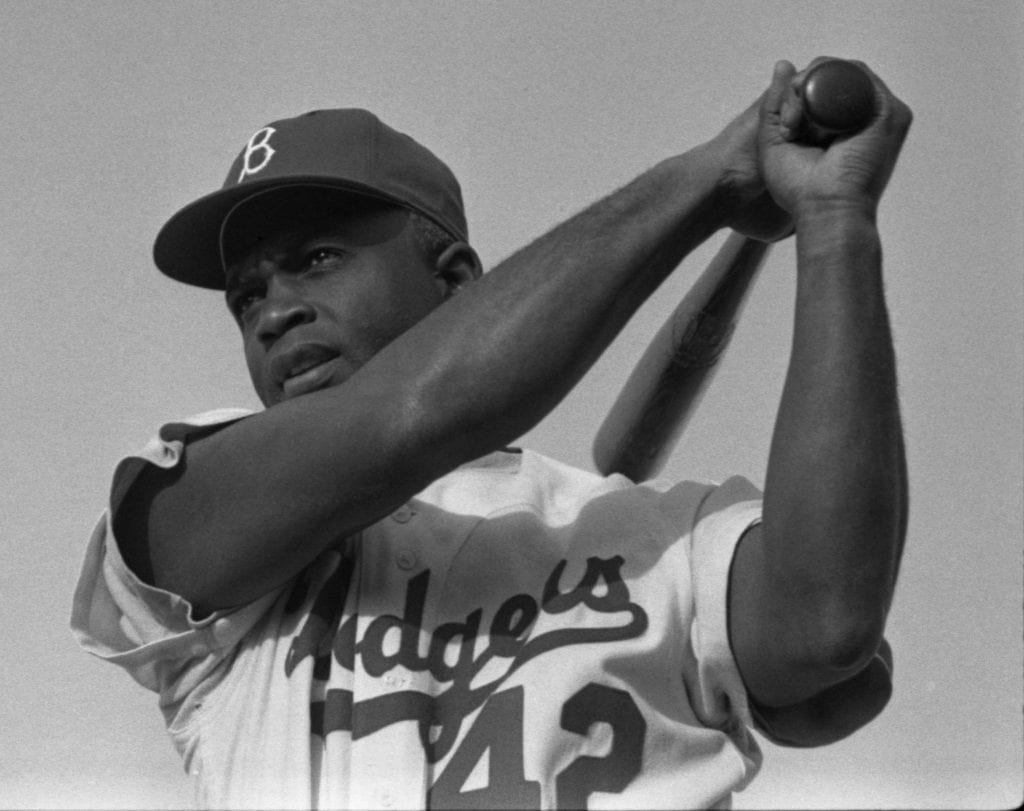 Jackie Robinson swings a baseball bat
