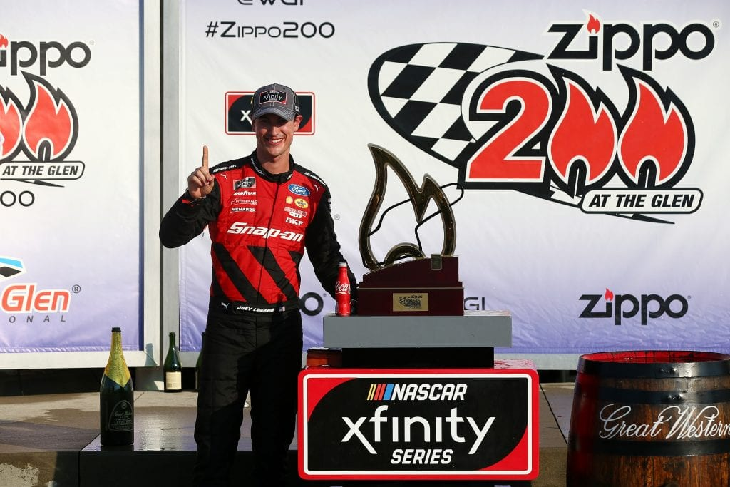 Joey Logano, driver of the #22 Snap On Ford, celebrates with the trophy in Victory Lane after winning the NASCAR Xfinity Series