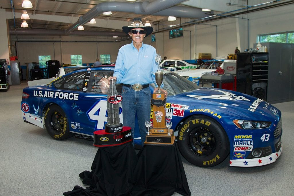 NASCAR Hall of Famer Richard Petty poses with the trophies from the 2014 Coke Zero 400 and the 1984 Firecracker 400