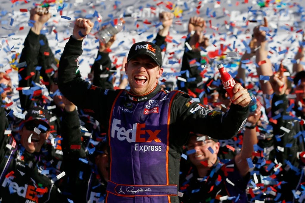 Denny Hamlin, driver of the #11 FedEx Express Toyota, celebrates in Victory Lane after winning the NASCAR Sprint Cup Series DAYTONA 500 at Daytona International Speedway