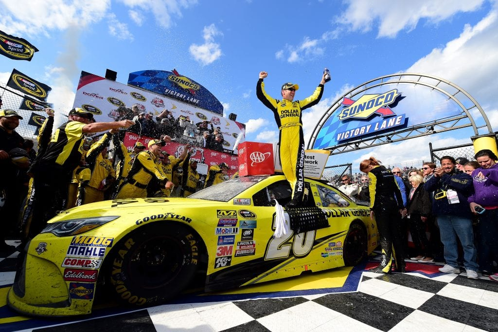 Matt Kenseth, driver of the #20 Dollar General Toyota, celebrates in Victory Lane after winning the NASCAR Sprint Cup Series AAA 400 Drive for Autism