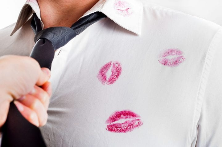 Man wearing white shirt covered by red lipstick kisses