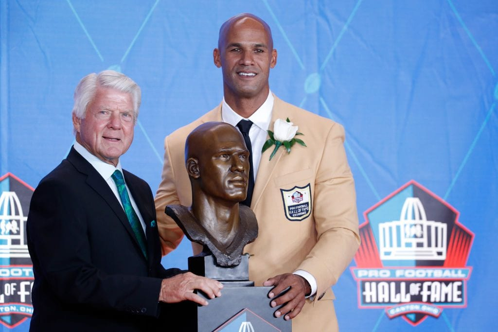 Jason Taylor and presenter Jimmie Johnson pose with Taylor's bust during the Pro Football Hall of Fame Enshrinement Ceremony at Tom Benson Hall of Fame Stadium in Canton, Ohio.