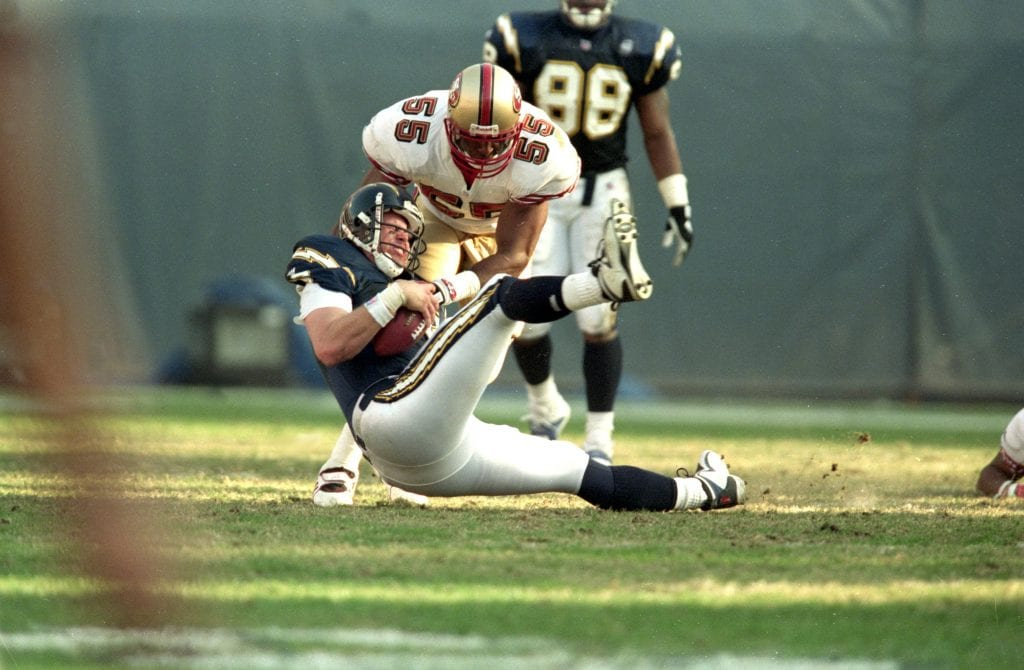 Winfred Tubbs #55 of the San Francisco 49ers tries to get the ball from Ryan Leaf #2 of the San Diego Chargers