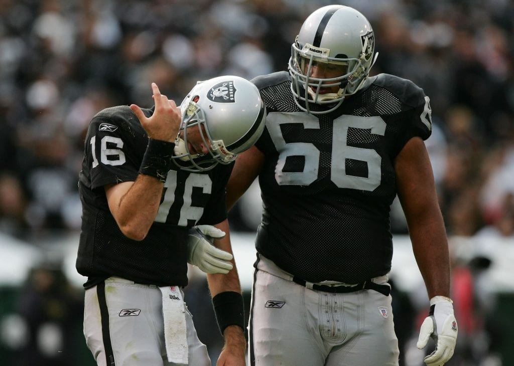 Andrew Walter #16 of the Oakland Raiders inspects his arm after a play as Langston Walker #66