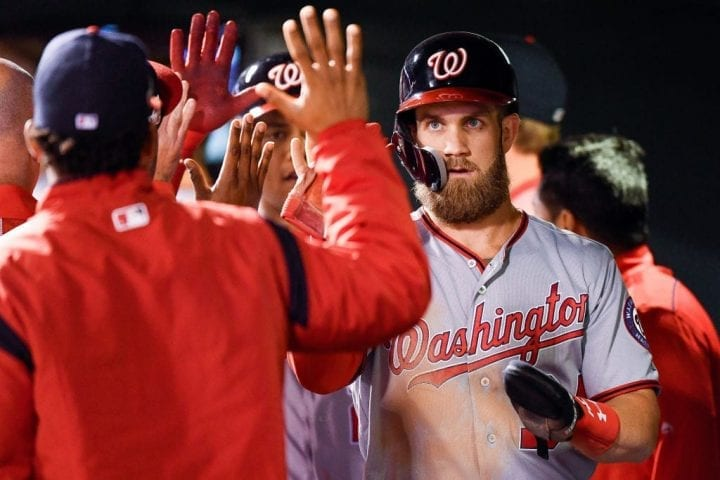 DENVER, CO - SEPTEMBER 29: Bryce Harper #34 of the Washington Nationals is congratulated in the dugout after scoring a seventh inning run against the Colorado Rockies at Coors Field on September 29, 2018 in Denver, Colorado. (Photo by Dustin Bradford/Getty Images)