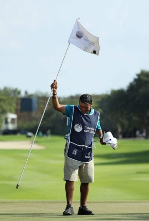 PLAYA DEL CARMEN, MEXICO - NOVEMBER 11: El Tucan, caddie for Matt Kuchar of the United States holds the pin flag on the 18th green after Kuchar won in the final round of the Mayakoba Golf Classic at El Camaleon Mayakoba Golf Course on November 11, 2018 in Playa del Carmen, Mexico. (Photo by Rob Carr/Getty Images)
