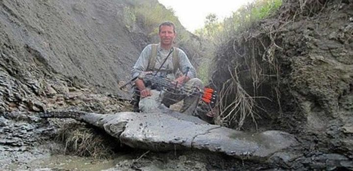 man stands in front of fossil with bow