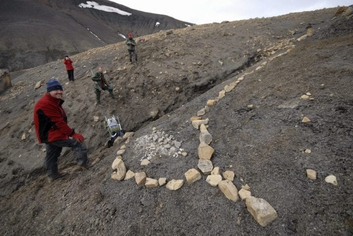 people stand next to archaeological site
