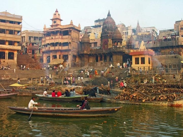 a gross river in india witt boats wading through it