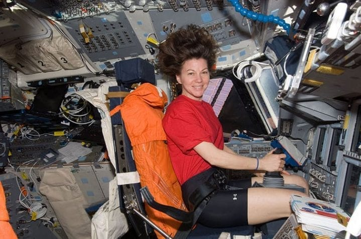 Female astronaut in zero gravity sitting in cockpit of space shuttle
