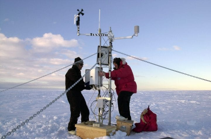 Researchers in the arctic outside setting up equipment