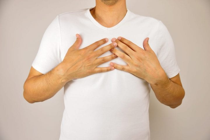 man with both hands on breast because of hard breathing and angina pectoris on grey background