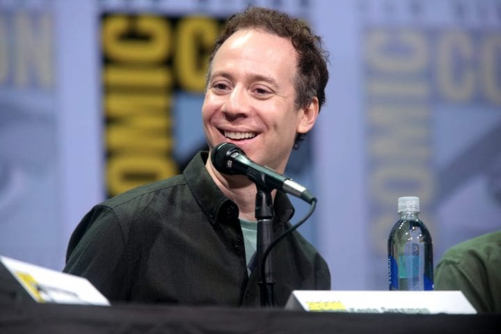 a man smiling into a microphone