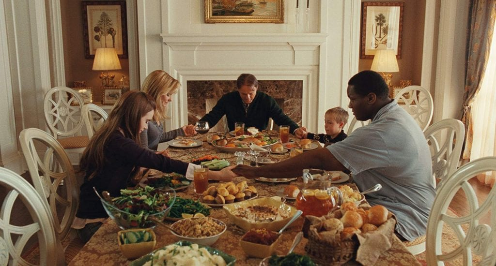 Michael Oher and the Tuohy family pray before a meal