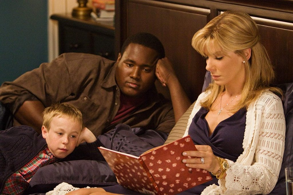 Sandra Bullock, playing Michael Oher's mother, reads a book to her children