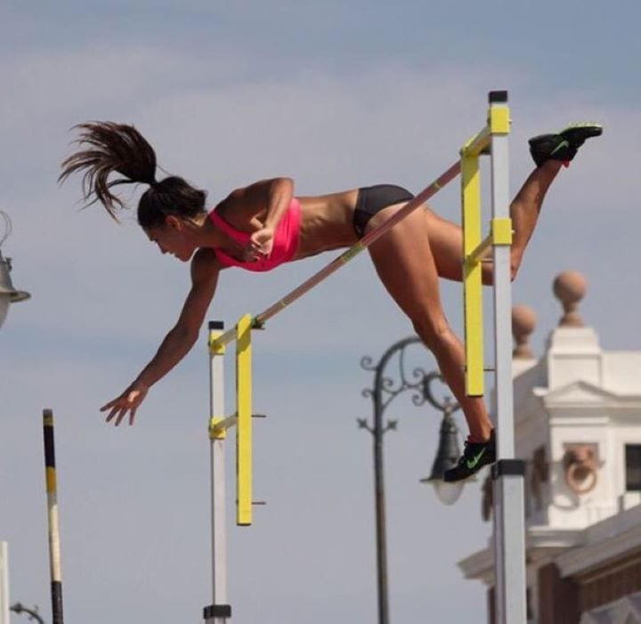 Allison Stokke reaches as far as she can as she attempts to clear the bar