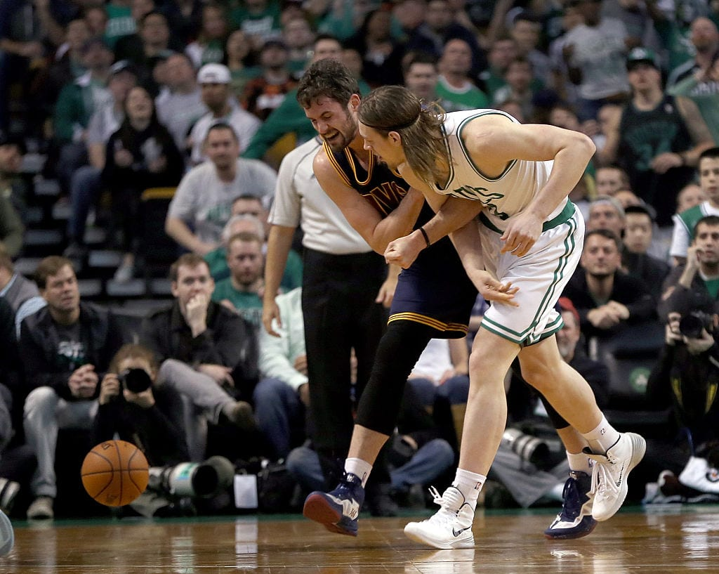 Kevin Love #0 of the Cleveland Cavaliers injures his shoulder as he chases a loose ball against Kelly Olynyk #41 of the Boston Celtics in the first half in Game Four during the first round of the 2015 NBA Playoffs on April 26, 2015 at TD Garden in Boston, Massachusetts.