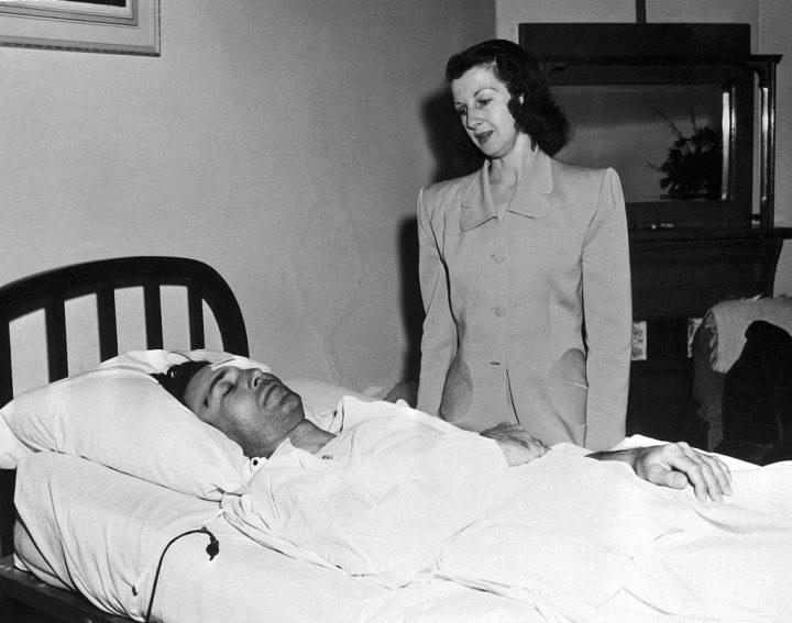 Mrs. Valerie Hogan stands at the bedside of her husband, pro golfer Ben Hogan, as he rests in his hospital bed at El Paso.