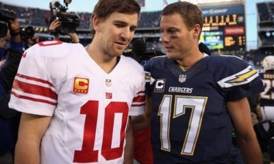 Eli Manning #10 of the New York Giants and Philip Rivers #17 of the San Diego Chargers come together