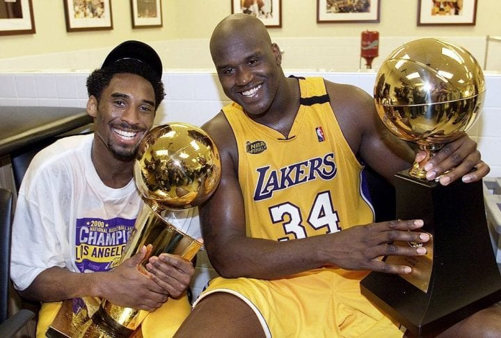 Kobe Bryant (L) of the Los Angeles Lakers holds the Larry O'Brian trophy as teammate Shaquille O'Neal (L) hold the MVP trophy