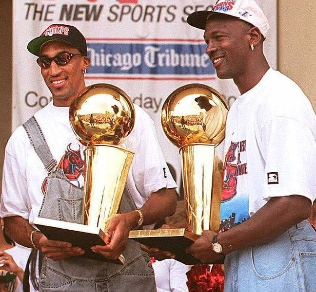 Chicago Bulls players Scottie Pippen (L) and Michael Jordan (R) hold two of the team's four recent Larry O'Brien trophies