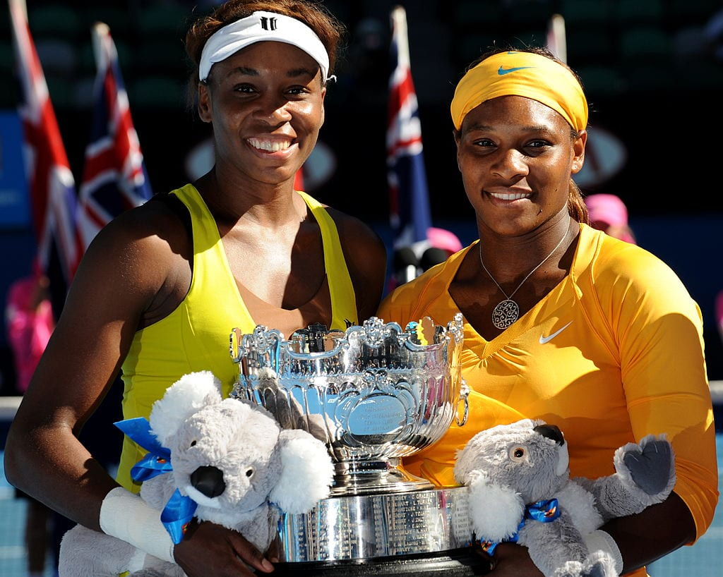 US tennis player Venus Williams (L) and her sister Serena Williams pose with the trophy after victory in their women's doubles finals