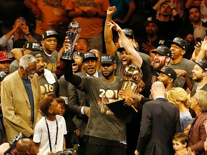 LeBron James hoists the Larry O'Brien and the Finals MVP trophies