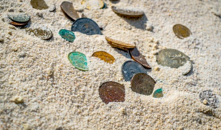 old coins partially buried in white sand
