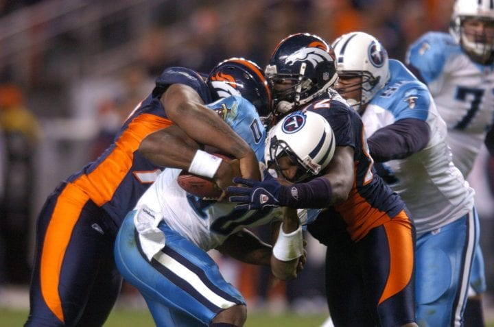 Denver Broncos Marcus Thomas (79) and Elvis Dumervil (92) swarm Tennessee Titans QB Vince Young