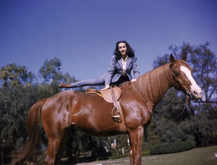 British-born actor Elizabeth Taylor swings her leg over a horse as she mounts it, 1947. (Photo by Getty Images)